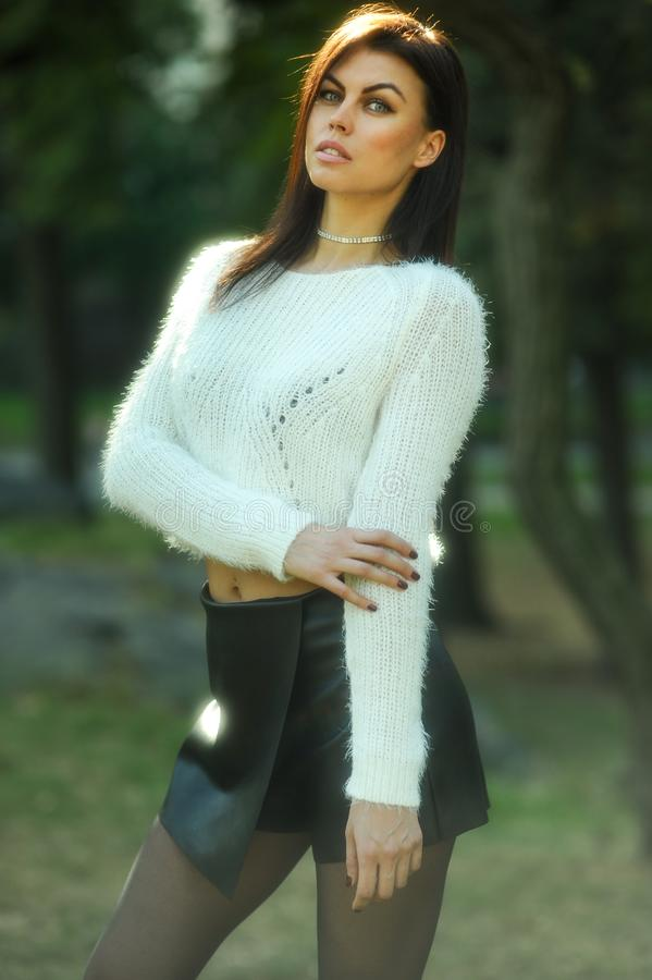 Piękna elegancka kobieta jest ubranym wygodnego pulower i mini spódnicę pozuje dosyć plenerowego obraz royalty free