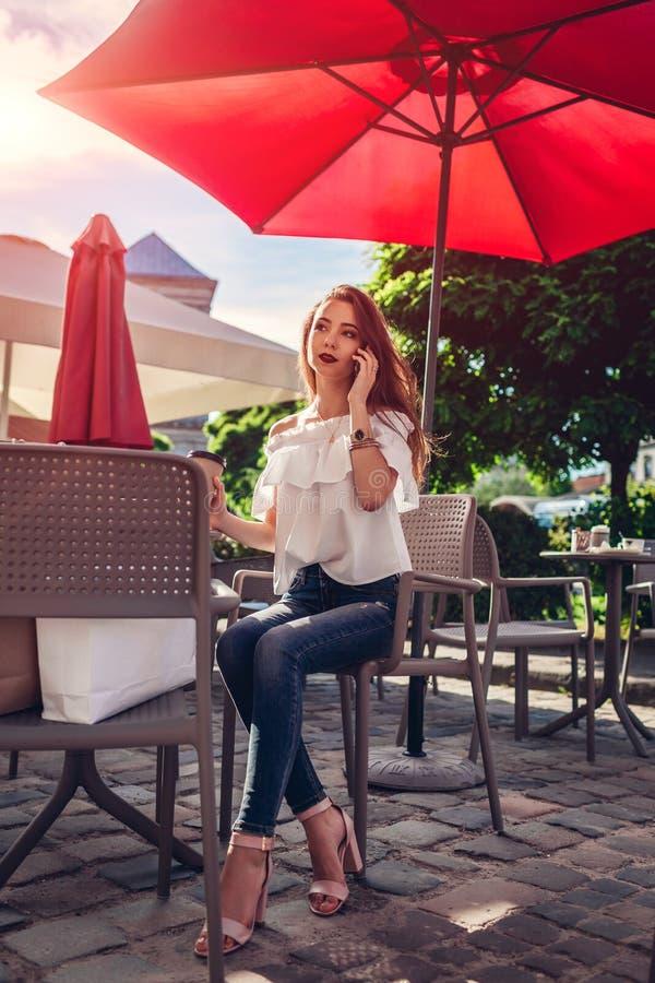 Piękna elegancka młoda kobieta chłodzi w plenerowej kawiarni na miasto ulicie i opowiada na telefonie z torba na zakupy obrazy royalty free