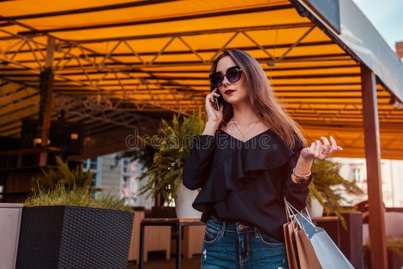 Piękna elegancka młoda kobieta chodzi kawiarnią na miasto ulicie i opowiada na telefonie z torba na zakupy fotografia stock