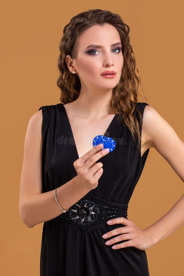 Piękna elegancka młoda kobieta z grzebaków układami scalonymi w ręce, na beżowym tle zdjęcie stock