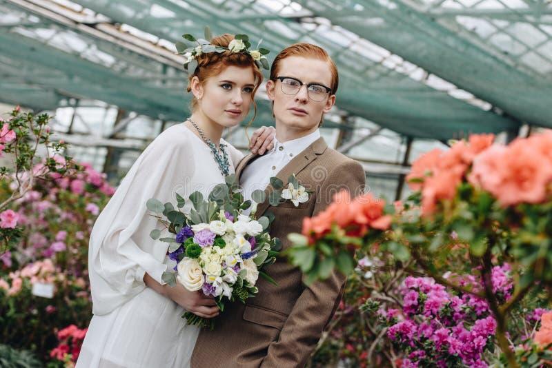 piękna elegancka młoda miedzianowłosa ślub para stoi wpólnie między kwiatami zdjęcia stock
