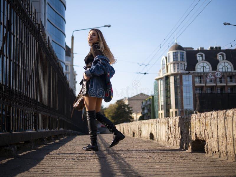 Piękna elegancka nastolatek dziewczyna z bieżącym włosy w pełnym przyroscie na miasto moście obraz stock