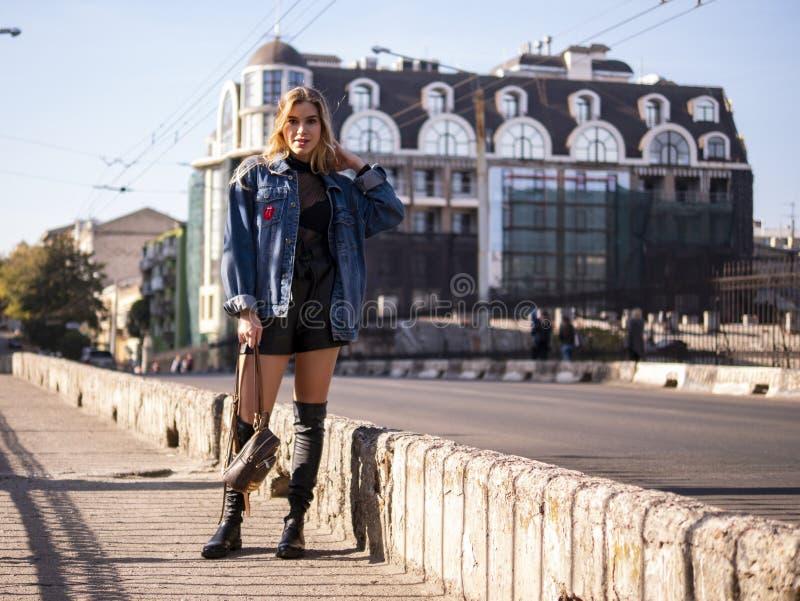 Piękna elegancka nastolatek dziewczyna z bieżącym włosy w pełnym przyroscie na miasto moście zdjęcia stock