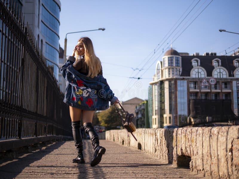 Piękna elegancka nastolatek dziewczyna z bieżącym włosy w pełnym przyroscie na miasto moście zdjęcie royalty free