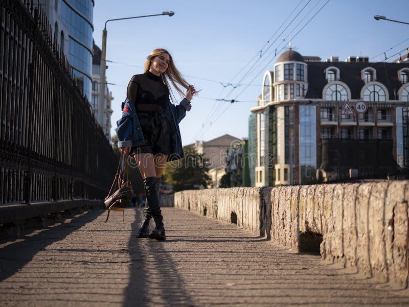 Piękna elegancka nastolatek dziewczyna z bieżącym włosy w pełnym przyroscie na miasto moście obraz royalty free