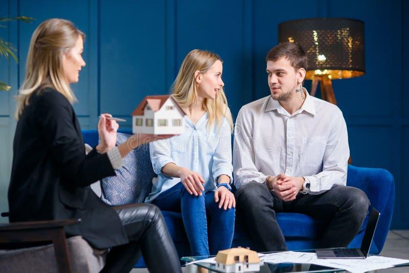 Piękna elegancka rodzina na spotkaniu z projektantem, pośrednik handlu nieruchomościami w eleganckim błękitnym biurze fotografia royalty free