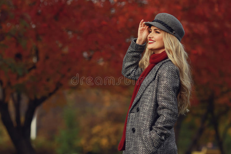 Piękna eleganckiej kobiety pozycja w modnym beżowym kapeluszu w parku w jesieni Copyspace fotografia stock
