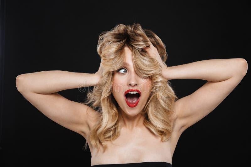 Piękna emocjonalna kobieta z jaskrawego makeup warg czerwony pozować odizolowywam nad czarnym tłem zdjęcie royalty free