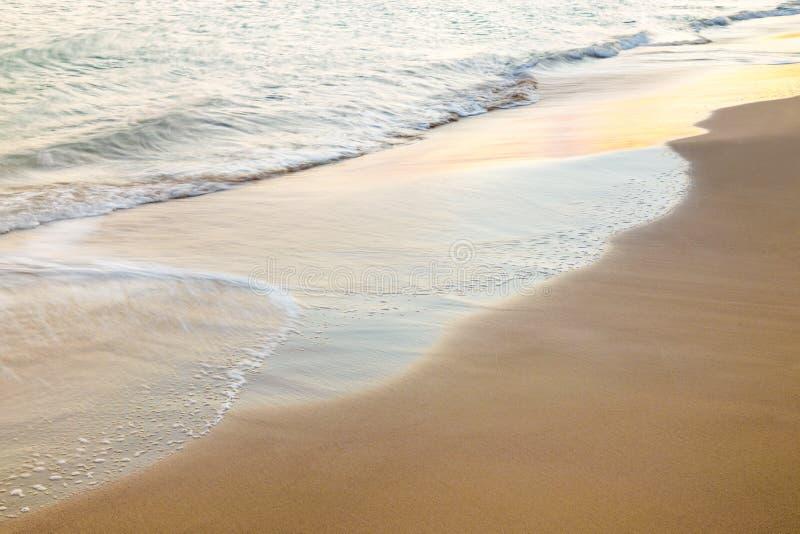 Piękna fala na piasek plaży przy zmierzchem fotografia stock