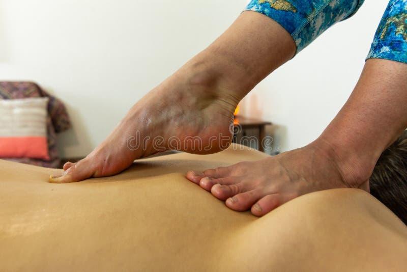 Piękna fotografia kobieta w kolorowych ubraniach daje głębokiemu tkankowemu nożnemu masażowi zdjęcia stock