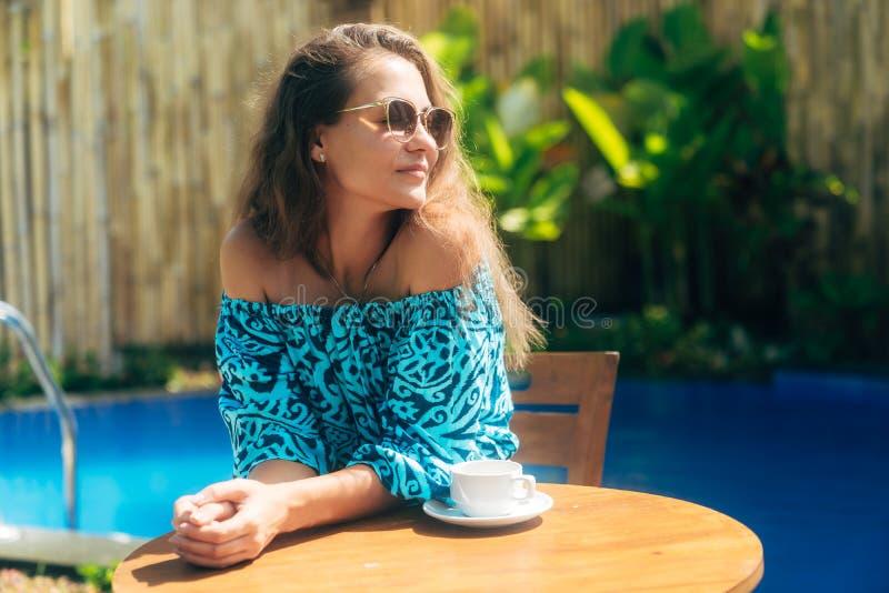 Piękna garbnikująca dziewczyna siedzi przy stołem z filiżanką herbata lub kawa w okularach przeciwsłonecznych M?oda kobieta ciesz obrazy royalty free