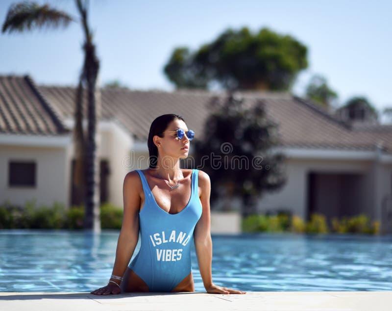 Piękna garbnikująca kobieta relaksuje w pływackiego basenu zdroju blisko drogiej willi na gorącym letnim dniu w błękitnym swimwea obrazy royalty free