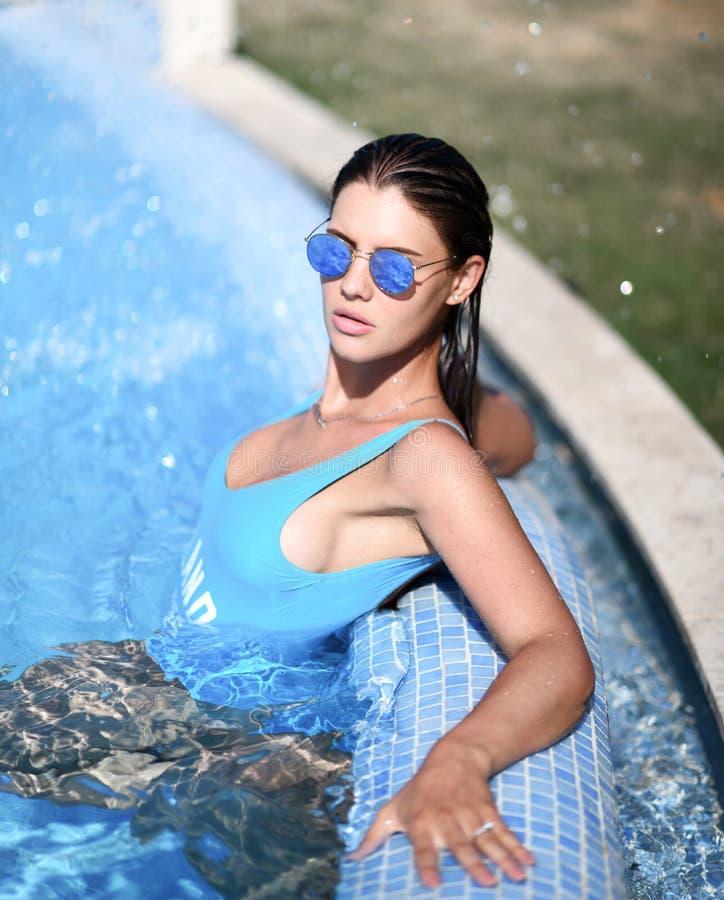 Piękna garbnikująca kobieta relaksuje w pływackiego basenu zdroju blisko drogiej willi na gorącym letnim dniu w błękitnym swimwea zdjęcie stock