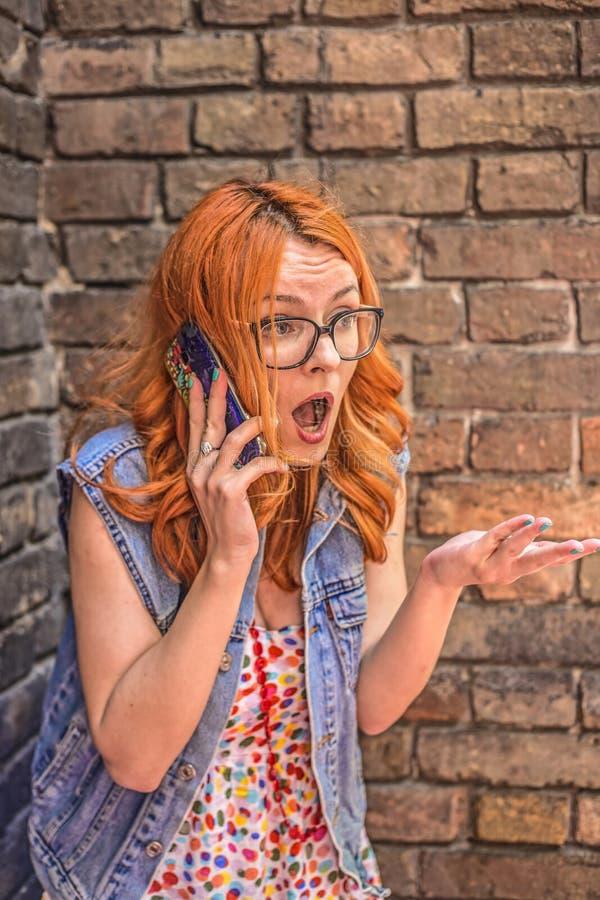 Piękna gniewnej i zmieszanej rudzielec Kaukaska dziewczyna opowiada na mądrze telefonie zdjęcia royalty free