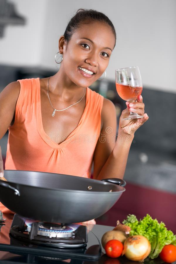Piękna gospodyni domowa z szkłem wina kucharstwo zdjęcie royalty free