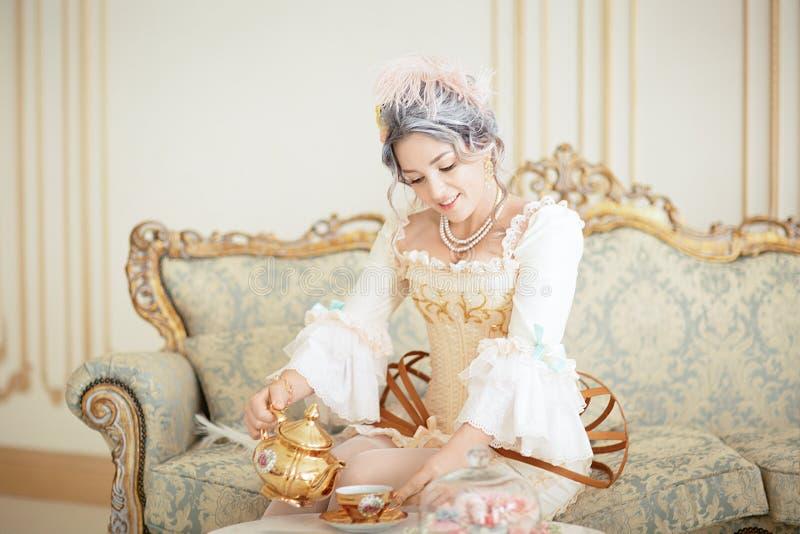 Piękna greyhead kobieta w rokoko smokingowy pozować przed różowym tłem podczas gdy nalewający herbaty od czajnika zdjęcie royalty free