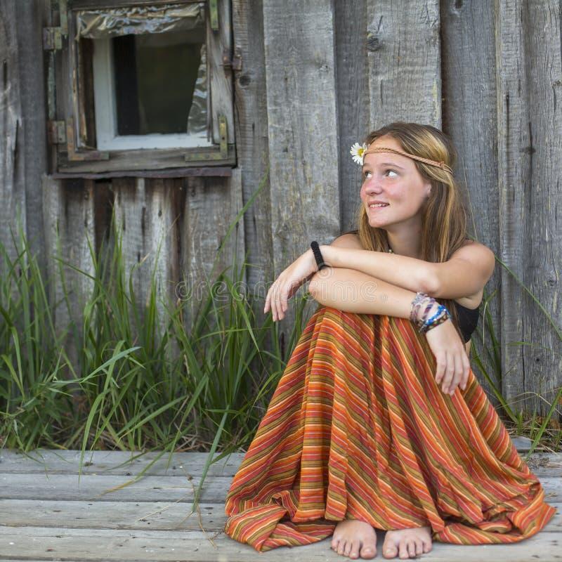 Piękna hipis dziewczyna siedzi outdoors w wsi, przyglądająca pusta przestrzeń na lewicie obraz stock