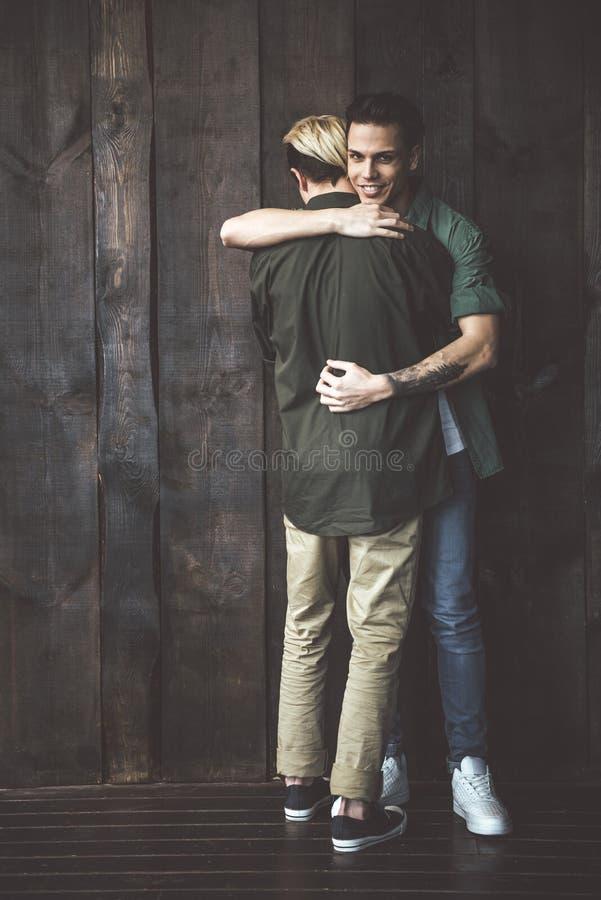 Piękna homoseksualna pary pozycja przeciw przytuleniu i ścianie obraz royalty free