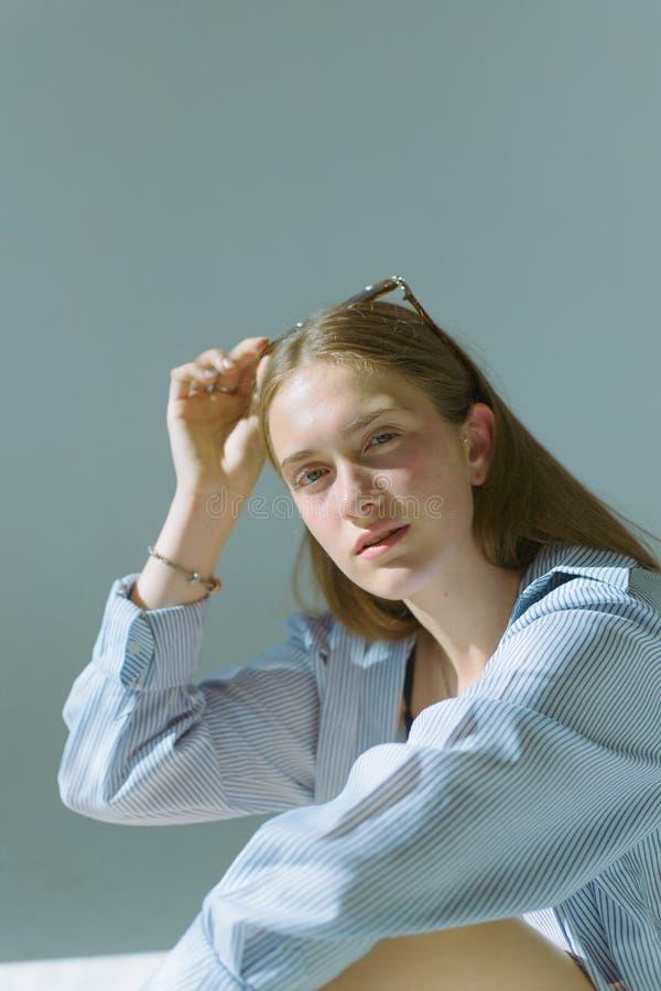 Piękna i atrakcyjna chuda dziewczyna w czarnej bieliźnie z długie włosy i są ubranym szkłami na białym tle, obraz stock