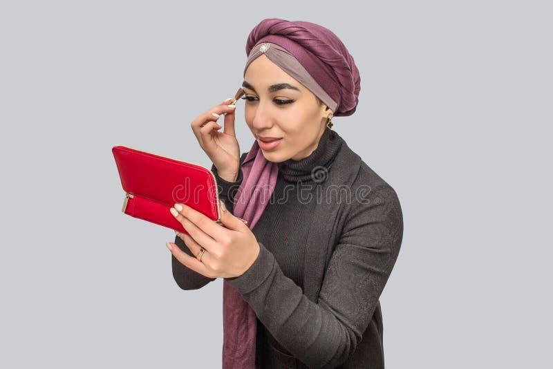 Piękna i atrakcyjna młoda arabska kobieta robi makeup Maluje ona i patrzeje w lustrze oczy Odizolowywający na popielatym zdjęcie stock