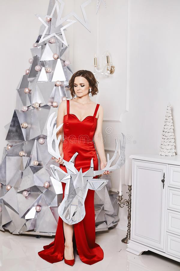 Piękna i długonoga wzorcowa dziewczyna w modnej czerwieni sukni w modnych czerwonych butach pozuje blisko srebra i fotografia royalty free