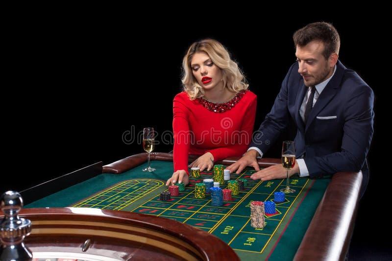 Piękna i dobrze ubierająca para bawić się ruletę w kasynie obrazy stock