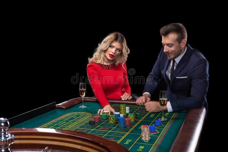 Piękna i dobrze ubierająca para bawić się ruletę w kasynie fotografia stock