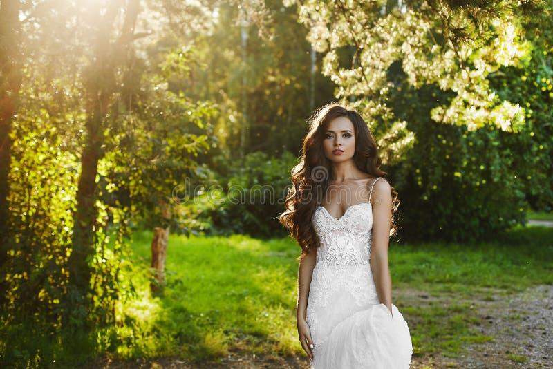 Piękna i młoda brunetka modela dziewczyna w białej koronkowej sukni, pozuje w parku przy zmierzchem obraz stock