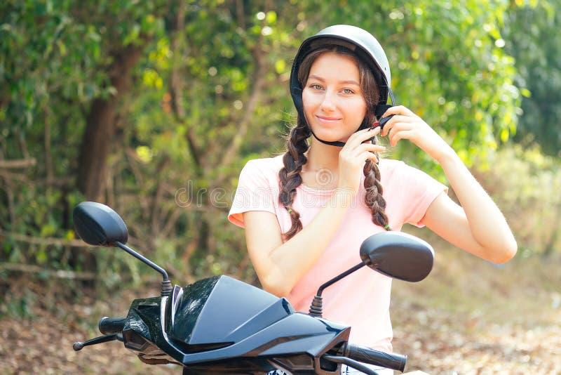 Piękna i młoda kobieta, siedząca na motocyklu w kask koncepcja bezpiecznej jazdy zdjęcia royalty free