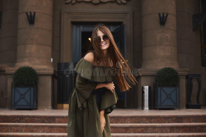 Piękna i modna brunetka modela dziewczyna z powabnym uśmiechem w eleganckiej sukni z nagimi ramionami w modnych sunglas i, zdjęcia stock
