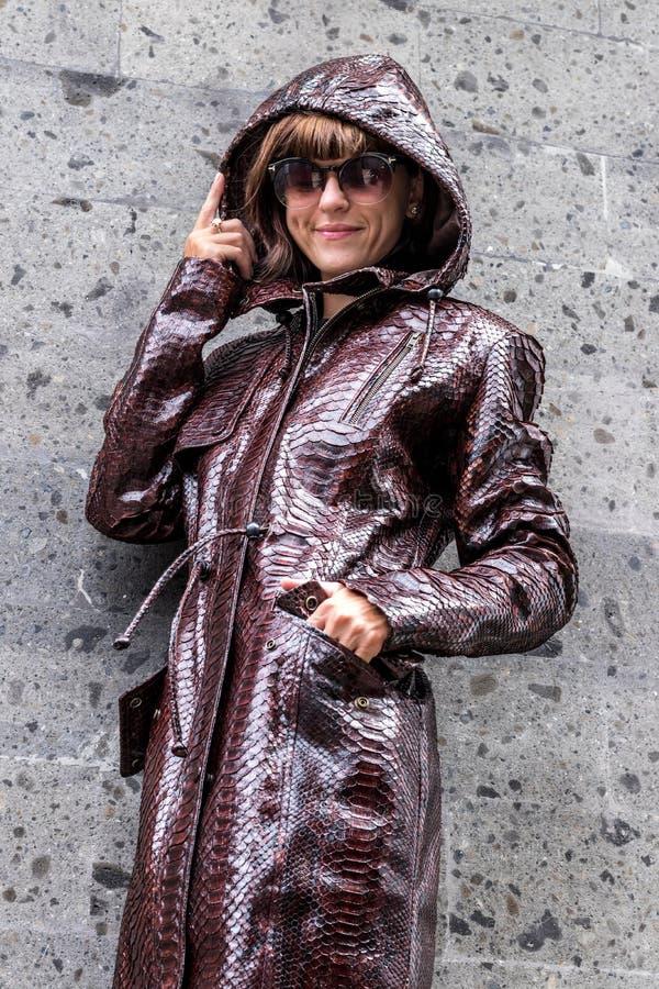 Piękna i modna młoda kobieta w długiej luksusowej snakeskin pytonu kurtce pozuje blisko popielatej ściany fotografia royalty free
