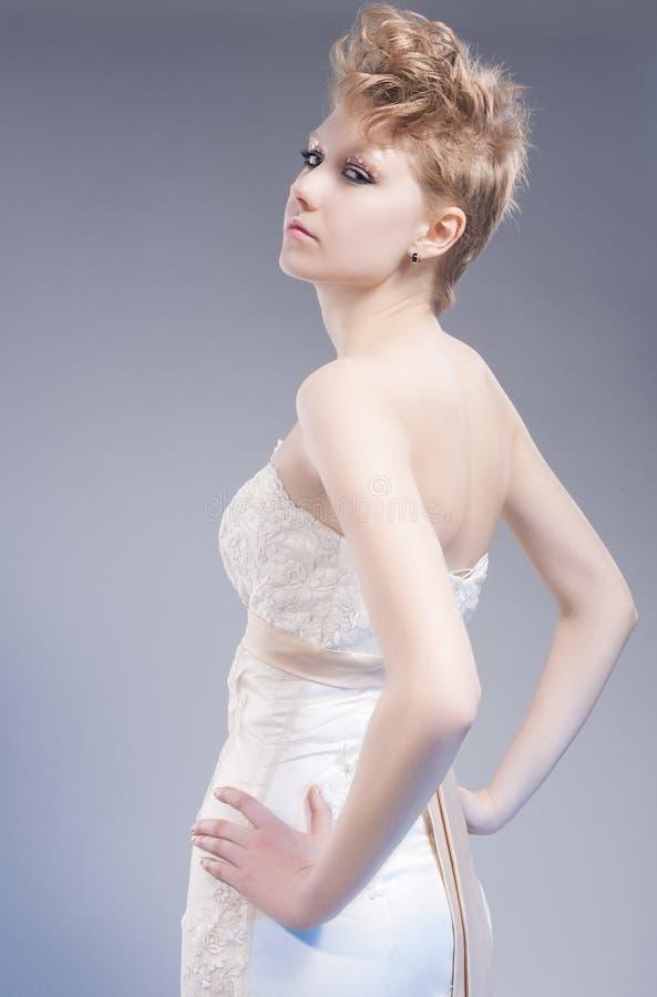 Piękna i mody pojęcia Młoda Seksowna Blond kobieta w Miło Dostosowywającej Ślubnej sukni Pozuje Przeciw szarość obrazy royalty free
