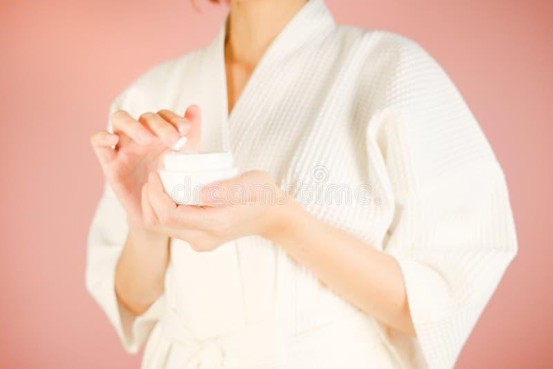 Piękna i mody różowy tło kobieta z kosmetykiem i skincare produktem twarzowa kremowa serum i moisturizer zawartość azjaci zdjęcia stock