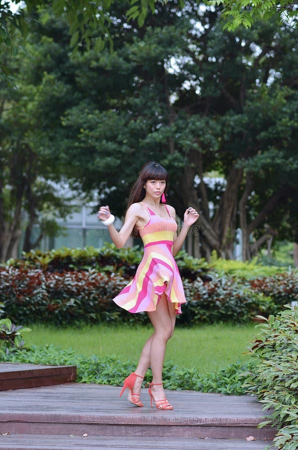 Piękna i płeć Azjatycka dziewczyna pokazuje ona młodości w parku obraz stock