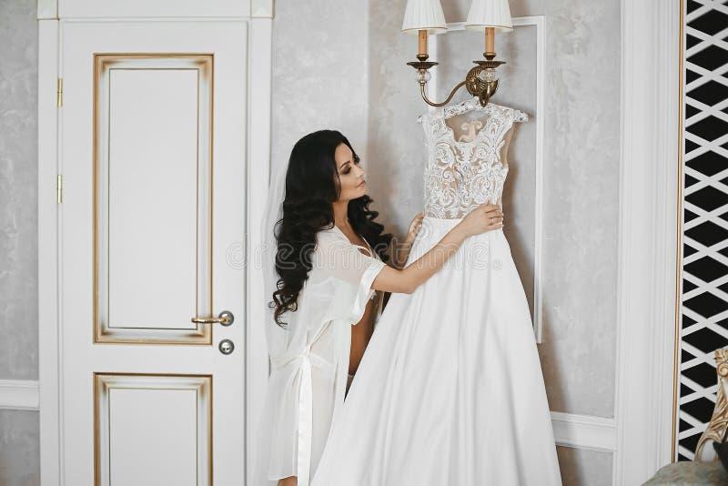 Piękna i seksowna brunetka modela dziewczyna z doskonalić ciałem w uwodzicielskim peignoir, patrzeje na jej ślubnej sukni przedte zdjęcie stock