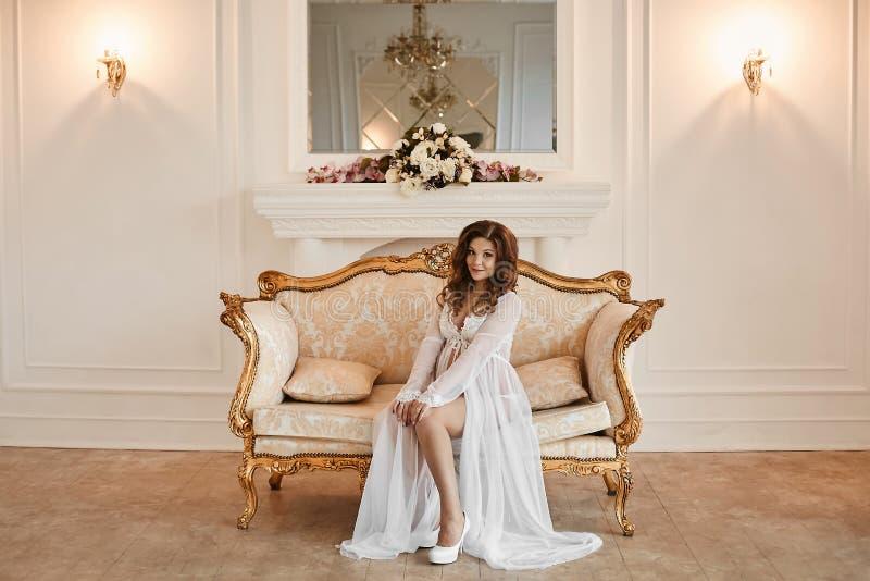 Piękna i seksowna młoda gestation kobieta w modnym peignoir siedzi na złocistej rocznik leżance przy luksusowym wnętrzem fotografia stock