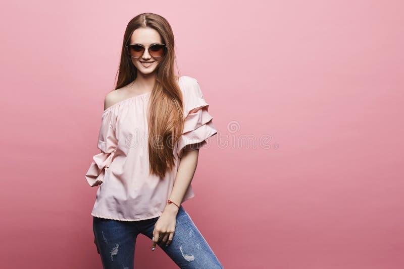 Piękna i seksowna wzorcowa blondynki dziewczyna w bluzce z nagimi ramionami w modnych różowych okularach przeciwsłonecznych i, po zdjęcia stock