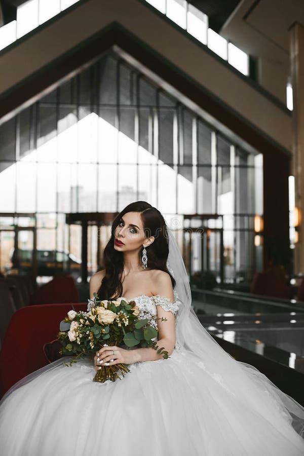 Piękna i seksowna wzorcowa kobieta z doskonalić ciałem i dużymi piersiami w modnej ślubnej sukni, trzyma eleganckiego fotografia stock