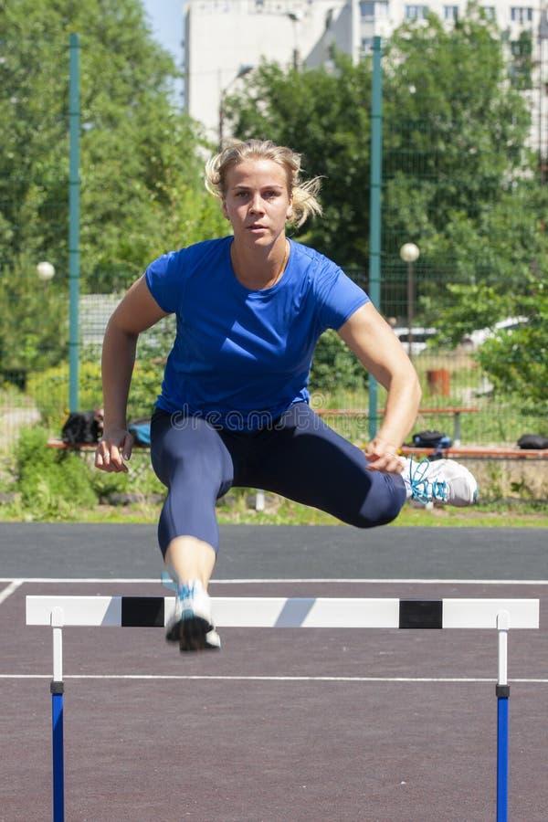 Pi?kna i sportowa dziewczyna biega przeszkody w stadium obraz royalty free