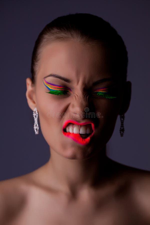 Piękna i złości kobiety portret z ultrafioletowymi kosmetykami obraz stock