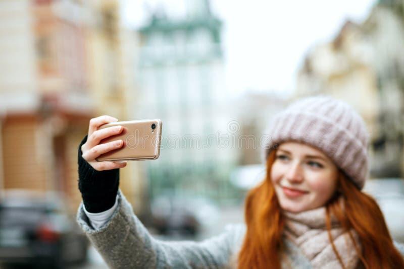 Piękna imbirowa kobieta w zimy odzieży bierze selfie na jej mo obrazy royalty free