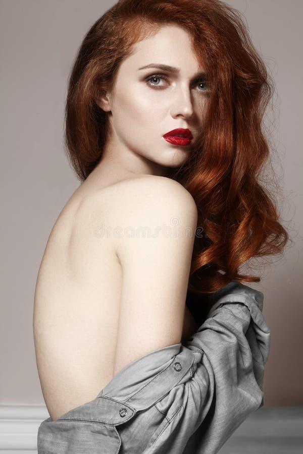 Piękna imbirowa młoda kobieta z luksusowym włosianym stylem i moda glancujemy makeup Piękna zbliżenia seksowny model z czerwonym  zdjęcia royalty free