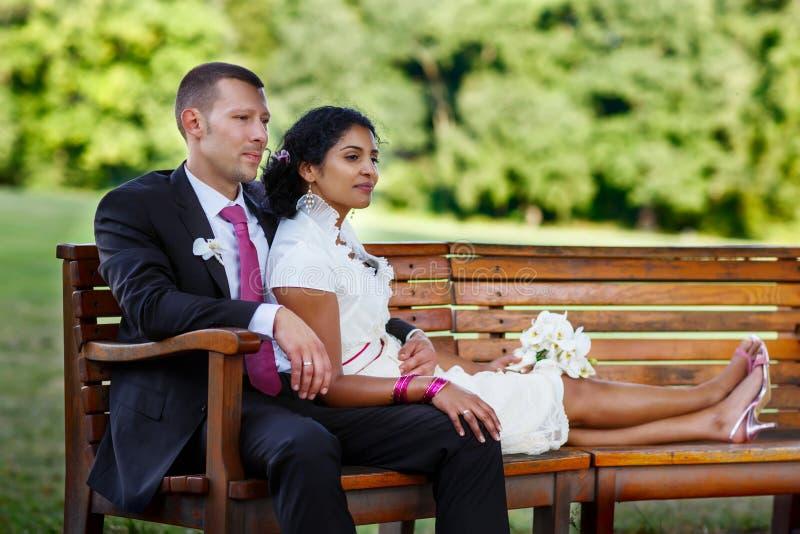Piękna indyjska panna młoda i caucasian fornal w lato parku, kwitnie szczęśliwych mienia kobiety potomstwa Młody człowiek ono uśm zdjęcia stock