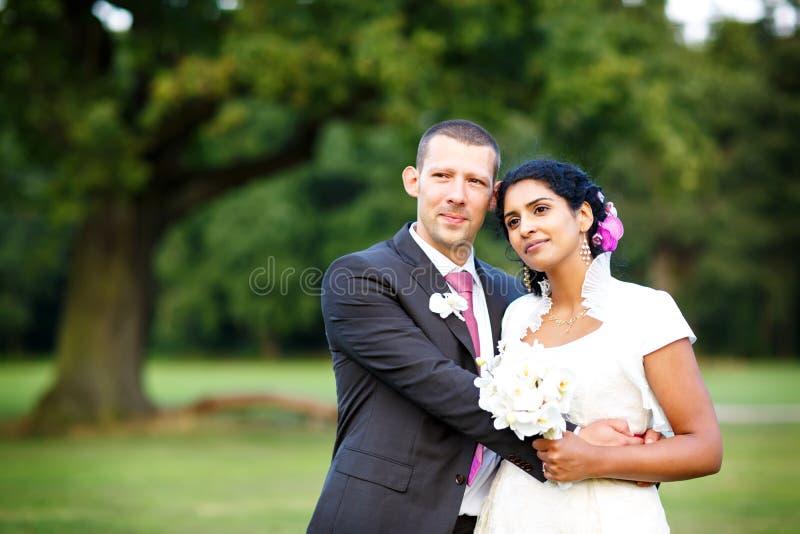Piękna indyjska panna młoda i caucasian fornal w lato parku, kwitnie szczęśliwych mienia kobiety potomstwa Młody człowiek ono uśm fotografia royalty free