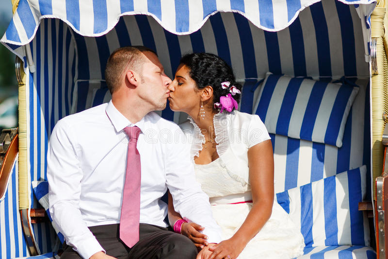 Piękna indyjska panna młoda i caucasian fornal w plażowym krześle. zdjęcie stock