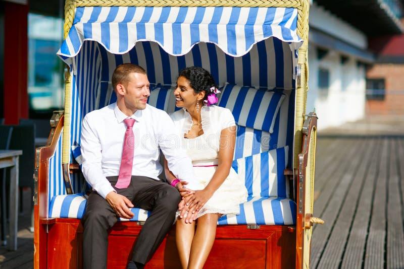 Piękna indyjska panna młoda i caucasian fornal w plażowym krześle, fotografia royalty free