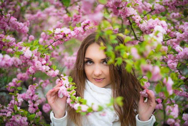 Piękna jasnogłowa dziewczyna z zielonymi oczami w białego żakieta i szalika białych stojakach w lesie w różowym czereśniowym okwi obrazy stock