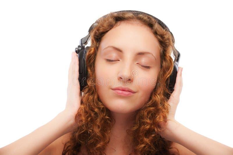 piękna kędzierzawa dziewczyna słucha obraz stock