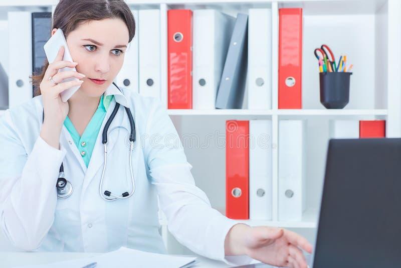 Piękna Kaukaska żeńska medycyny lekarka pracuje przy laptopem i opowiada telefonem komórkowym obrazy royalty free