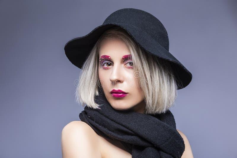 Piękna Kaukaska Blond dziewczyna w czarnym kapeluszu Nad Szarym tłem z Twarzowym makijażem zdjęcia royalty free